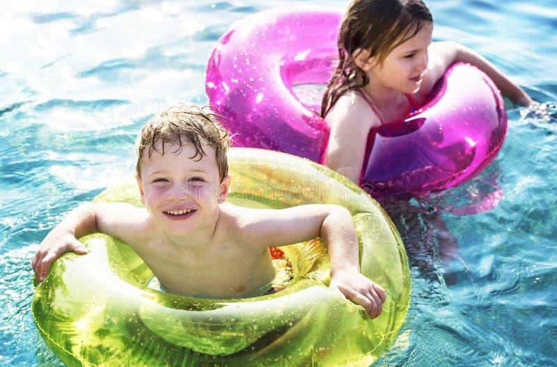 Vrolijke broer en zuster die in de pool zwemmen royalty-vrije stock afbeeldingen