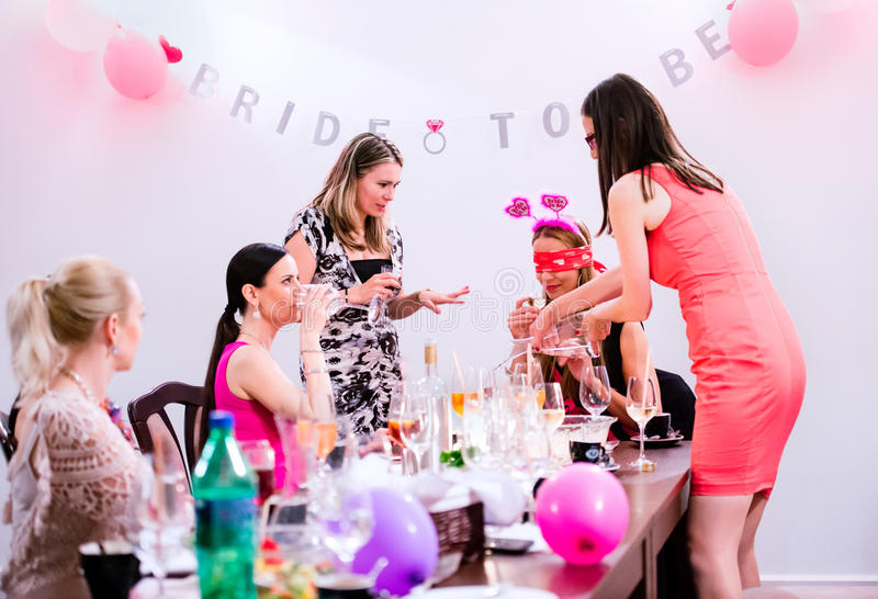 Vrolijke bruid en bruidsmeisjes die kippenpartij met dranken vieren stock afbeeldingen