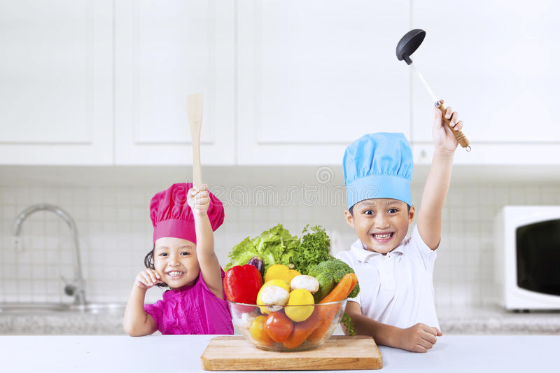 Vrolijke chef-kokjonge geitjes in keuken stock afbeeldingen