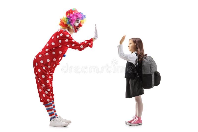Vrolijke clown die hoog-vijf met een schoolmeisje gesturing royalty-vrije stock afbeeldingen