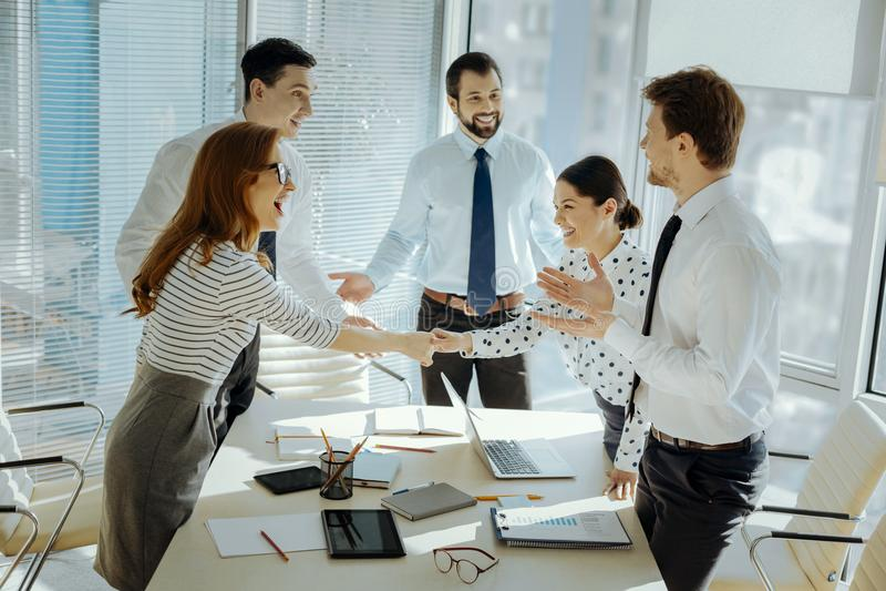 Vrolijke collega's die elkaar begroeten vóór commerciële vergadering stock afbeelding