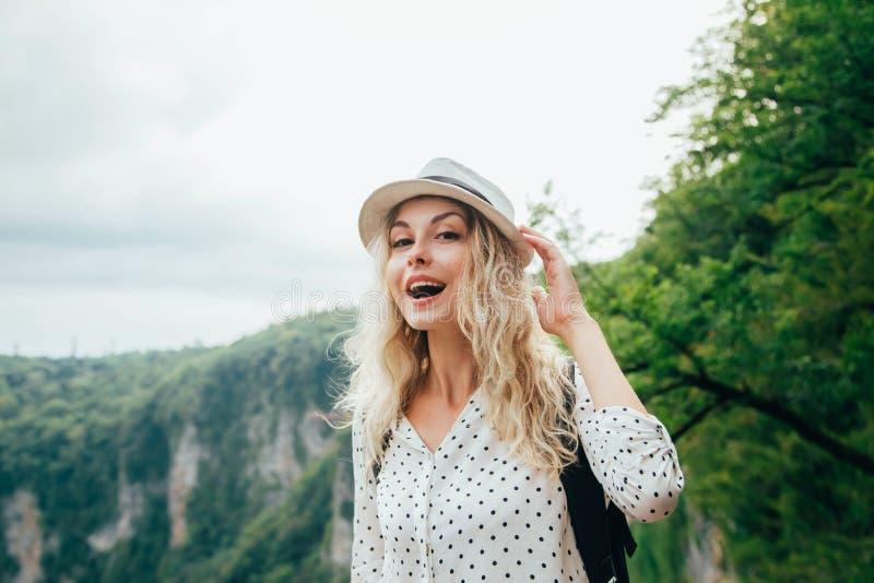 Vrolijke dame met blond stromend haar in een groot wit stipoverhemd die een hoed met haar hand, een gelukkige jonge vrouw houden royalty-vrije stock foto's