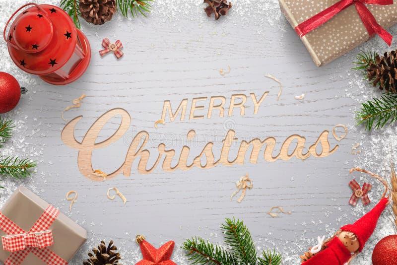 Vrolijke die Kerstmistekst in een houten die oppervlakte wordt gesneden en door Kerstmisdecoratie wordt omringd stock afbeeldingen