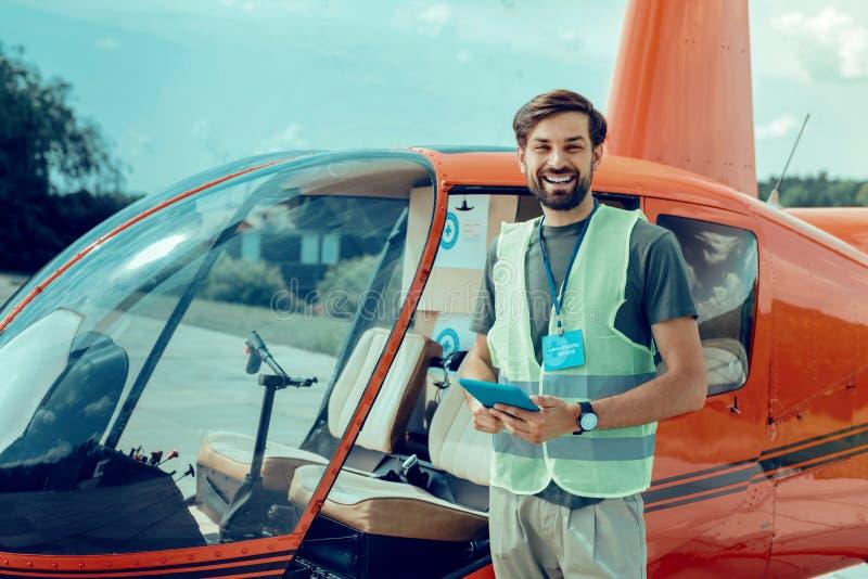 Vrolijke donker-haired vrijwilliger met brede glimlach die zich dichtbij helikopter bevinden royalty-vrije stock fotografie