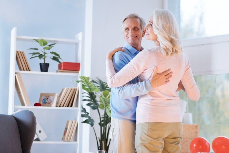 Vrolijke echtgenoot en vrouw die tijdens dans glimlachen stock afbeeldingen
