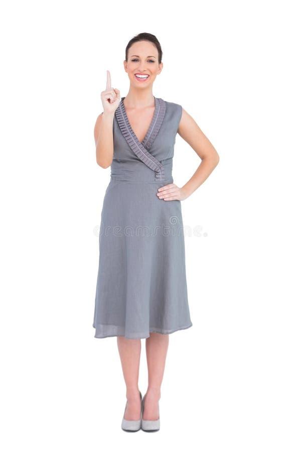 Vrolijke elegante vrouw die in elegante kleding haar vinger benadrukken stock afbeeldingen
