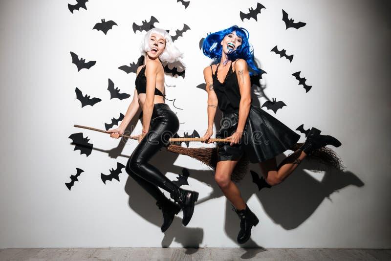 Vrolijke emotionele jonge vrouwen in Halloween-kostuums royalty-vrije stock foto