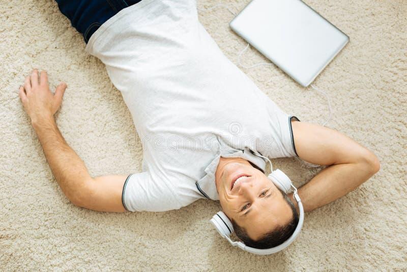 Vrolijke emotionele mens die terwijl het luisteren aan zijn favoriete muziek ontspannen stock afbeeldingen