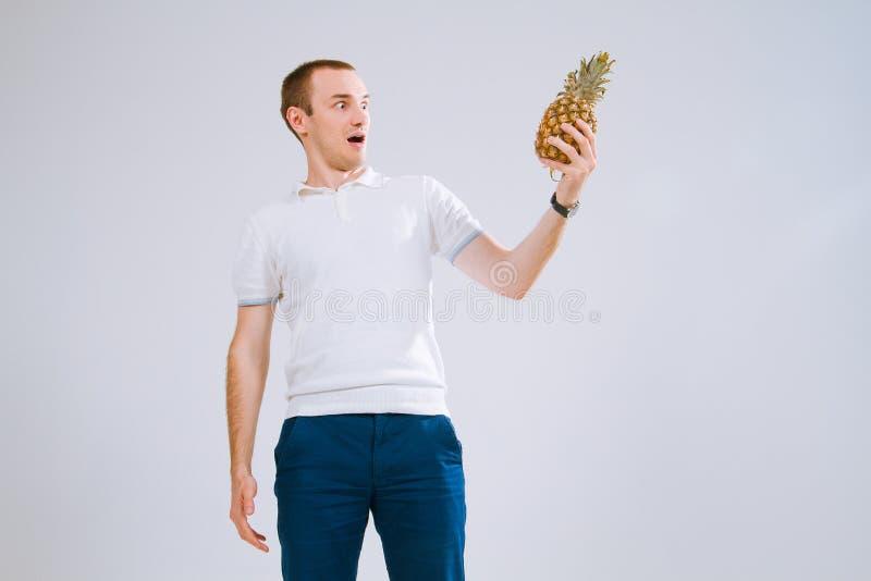 Vrolijke en emotionele kerel die een ananas in zijn hand op een witte achtergrond houden stock fotografie
