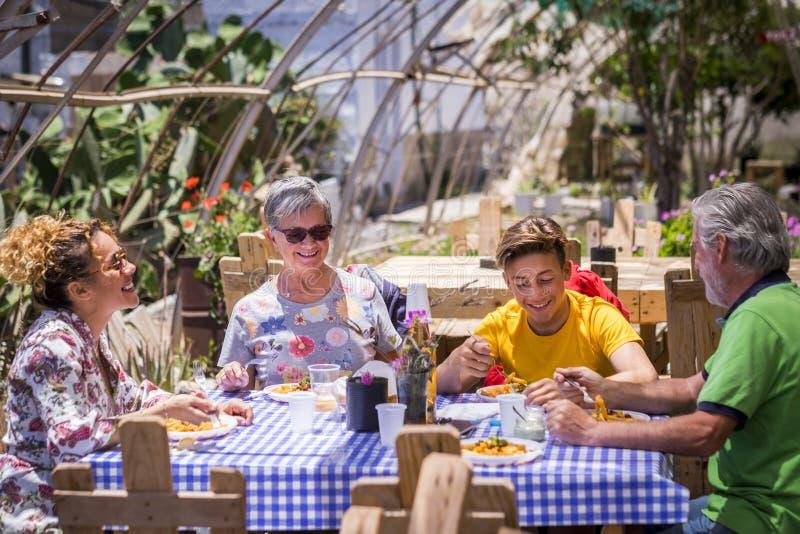 Vrolijke en gelukkige familie in alternatief openluchtrestaurant al natuurlijk en gemaakt met gerecycleerde houten pallets aardig stock fotografie