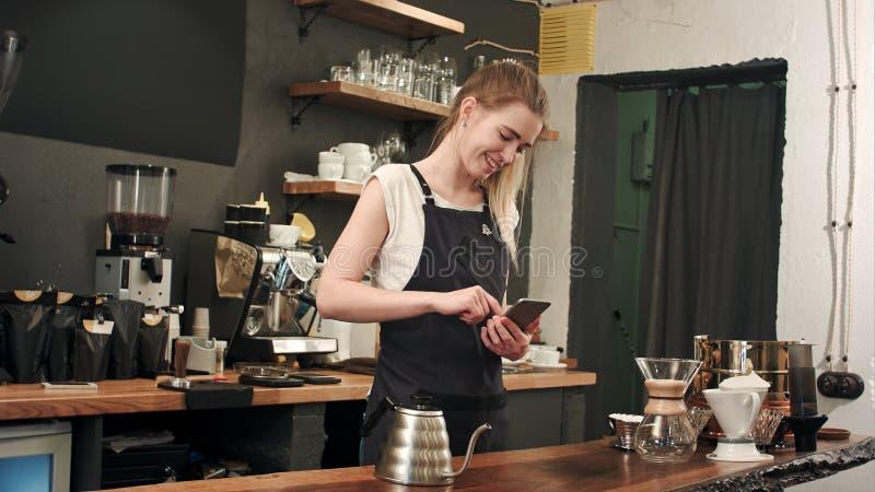 Vrolijke en inhouds vrouwelijke barista gebruikend mobiele telefoon en texting bij koffiewinkel royalty-vrije stock fotografie