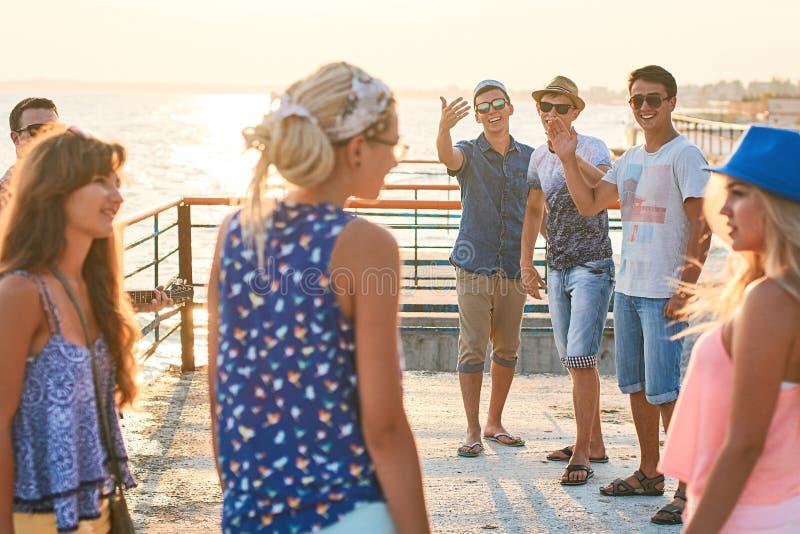 Vrolijke en onbezorgde groep vrienden die uit bij de zonnige de zomerkust hangen op hun vakantie stock foto's