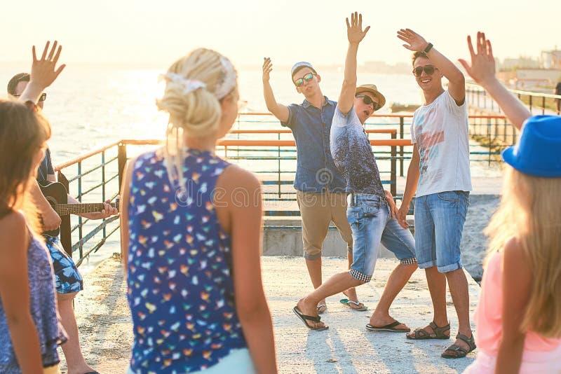 Vrolijke en onbezorgde groep vrienden die uit bij de zonnige de zomerkust hangen op hun vakantie royalty-vrije stock afbeeldingen