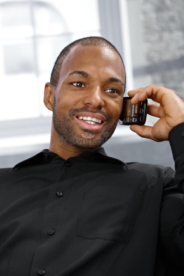 Vrolijke etnische mens op telefoongesprek stock afbeeldingen