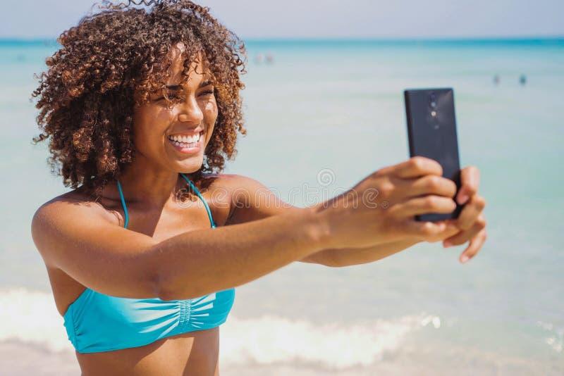 Vrolijke etnische vrouw die selfie op strand nemen stock foto