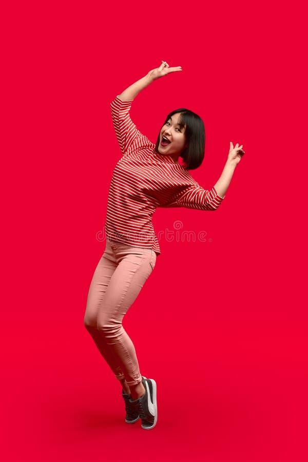 Vrolijke etnische vrouw die zich op tiptoe en gesturing V-teken bevinden stock foto