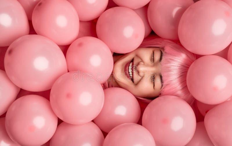 Vrolijke etnische vrouw in roze pruik die onder ballons liggen royalty-vrije stock foto's