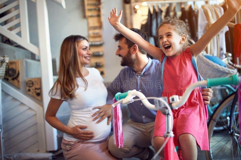 Vrolijke familie die nieuwe fiets kopen voor gelukkig meisje in fietswinkel royalty-vrije stock foto's