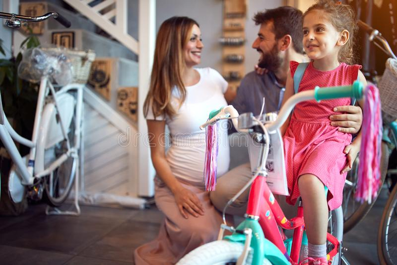 Vrolijke familie die nieuwe fiets kopen voor meisje in fietswinkel stock afbeelding