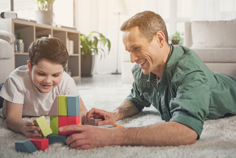Vrolijke familie die op vloer liggen en met stuk speelgoed spelen royalty-vrije stock afbeeldingen