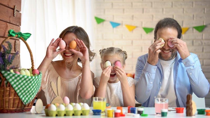 Vrolijke familie die pret hebben die voor Pasen voorbereidingen treffen en gekleurde eieren zetten aan ogen royalty-vrije stock foto