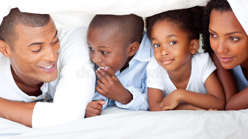 Vrolijke familie die pret heeft die op bed ligt stock foto's