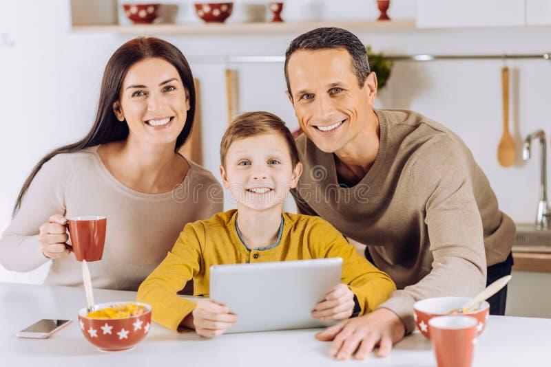 Vrolijke familie die terwijl het letten van op video op tablet stellen stock fotografie