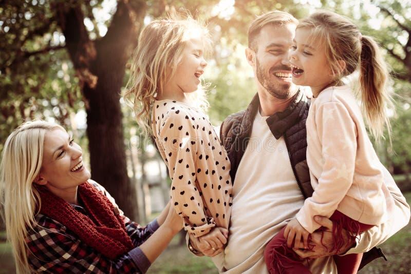 Vrolijke familie samen in park die in aard genieten van stock afbeeldingen