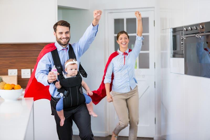 Vrolijke familie in superherokostuum met baby royalty-vrije stock fotografie