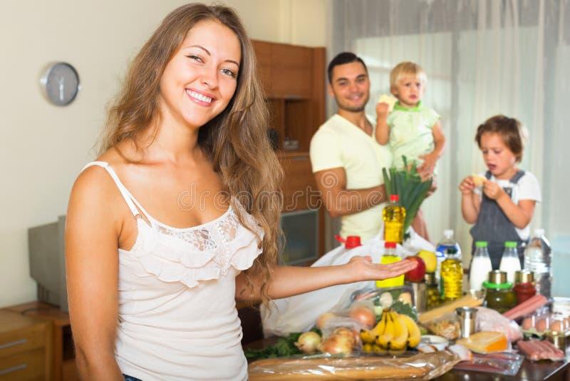 Vrolijke familie van vier met zakken voedsel stock fotografie