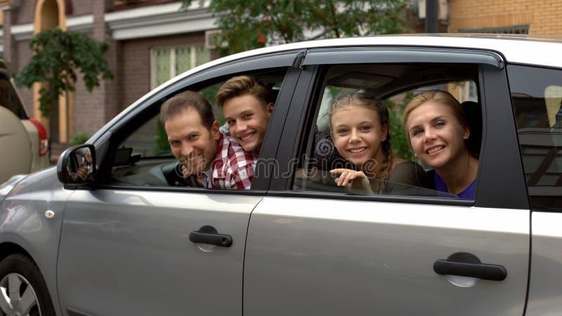 Vrolijke familiezitting in auto en het glimlachen in camera, autohuur, verzekering royalty-vrije stock afbeeldingen