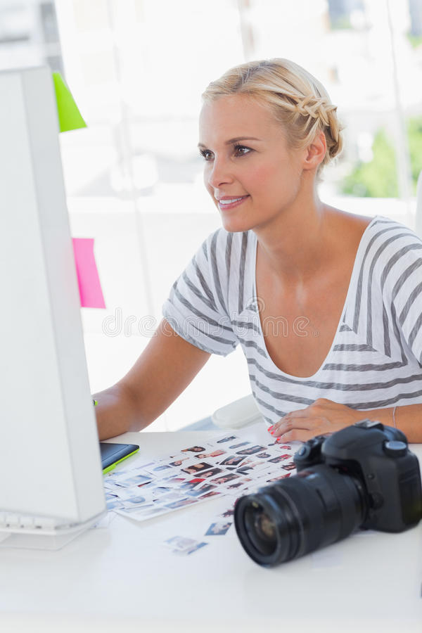 Vrolijke fotoredacteur die bij haar bureau werken stock foto's