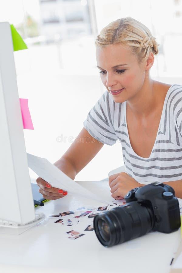 Vrolijke fotoredacteur die een contactblad bekijken stock fotografie