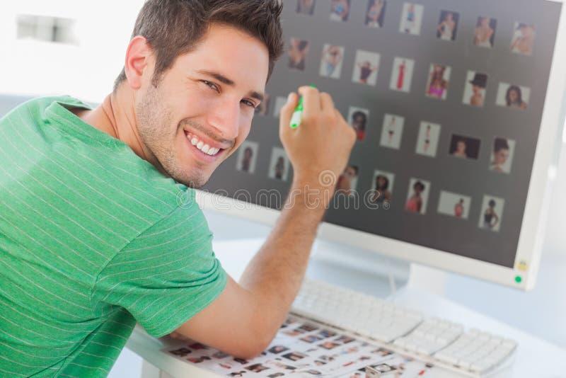 Vrolijke fotoredacteur die op het zijn scherm richten stock fotografie