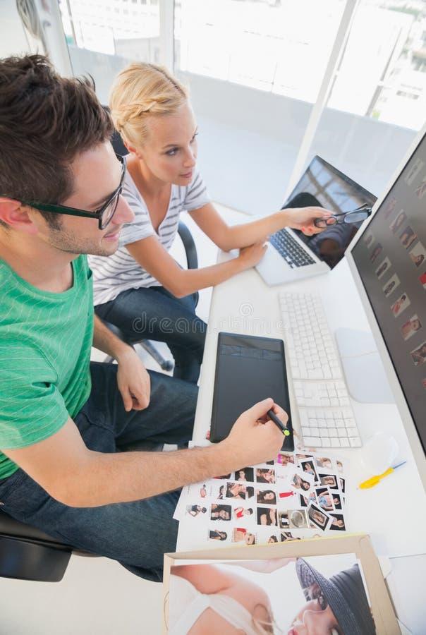 Vrolijke fotoredacteurs die aan grafiektablet samenwerken stock foto