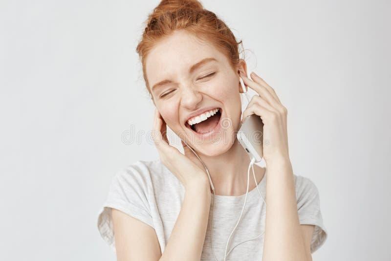 Vrolijke foxy meisje verheugende het luisteren muziek in hoofdtelefoons het glimlachen stock foto's