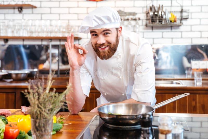 Vrolijke gebaarde chef-kokkok die en o.k. teken koken tonen royalty-vrije stock afbeeldingen