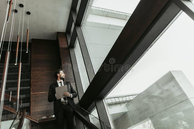 Vrolijke gebaarde mannelijke werkgever het schrijven informatie binnen royalty-vrije stock afbeelding