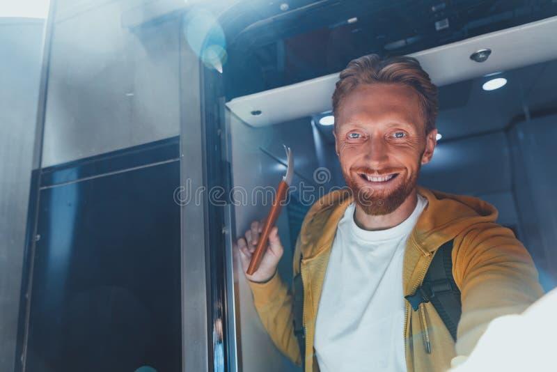 Vrolijke gebaarde mens die selfie bij trein maken stock afbeelding