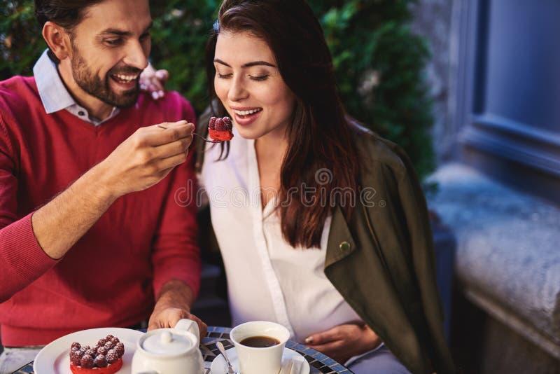 Vrolijke gebaarde mens die zijn charmant meisje met smakelijke cake voeden royalty-vrije stock fotografie
