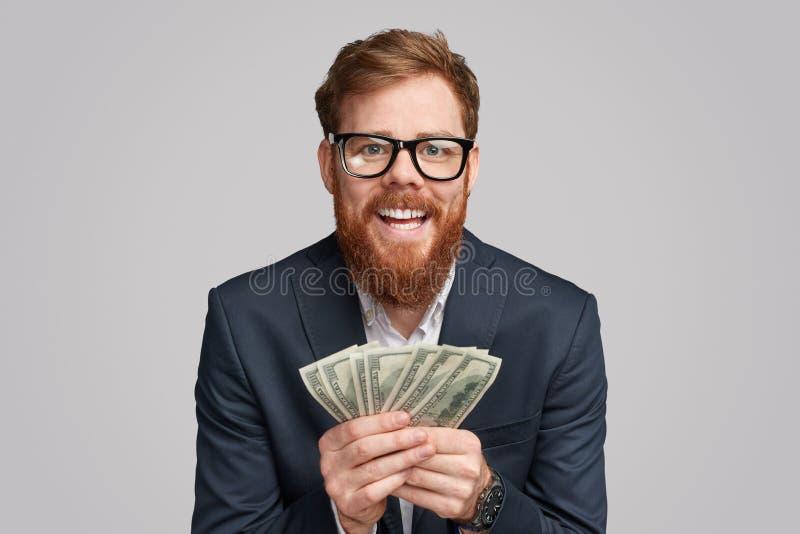 Vrolijke gebaarde mens met geld stock foto's