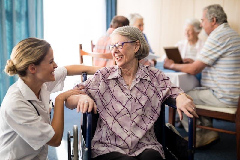 Vrolijke gehandicapte hogere vrouwenzitting op rolstoel die vrouwelijke arts bekijken stock foto's