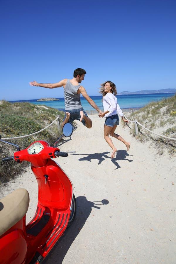 Vrolijke gelukkige paar het springen rubriek aan het strand royalty-vrije stock afbeelding