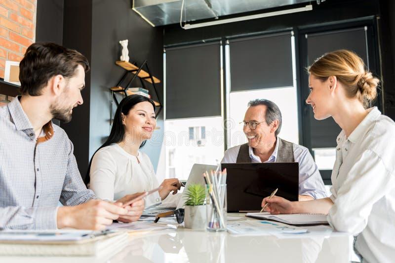 Vrolijke gelukkige werknemers die in bureau samenwerken royalty-vrije stock afbeelding