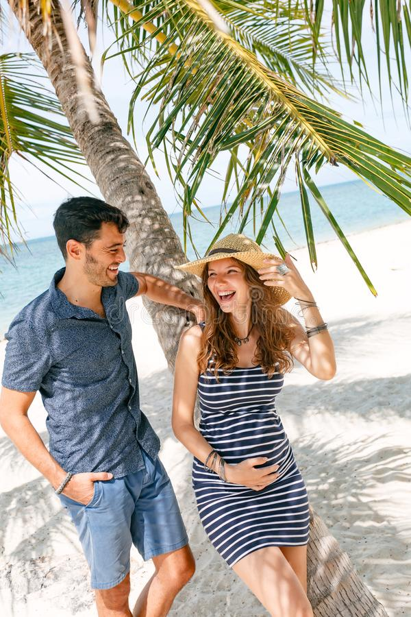 Vrolijke gelukkige zwangere vrouw en echtgenoot die pret op beac hebben royalty-vrije stock afbeelding
