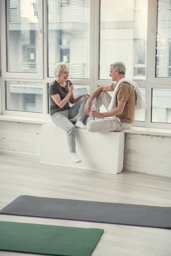 Vrolijke gepensioneerden die op vensterbank zitten royalty-vrije stock fotografie