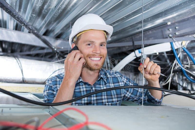 Vrolijke glimlachende bouwer die in plafond werken royalty-vrije stock foto