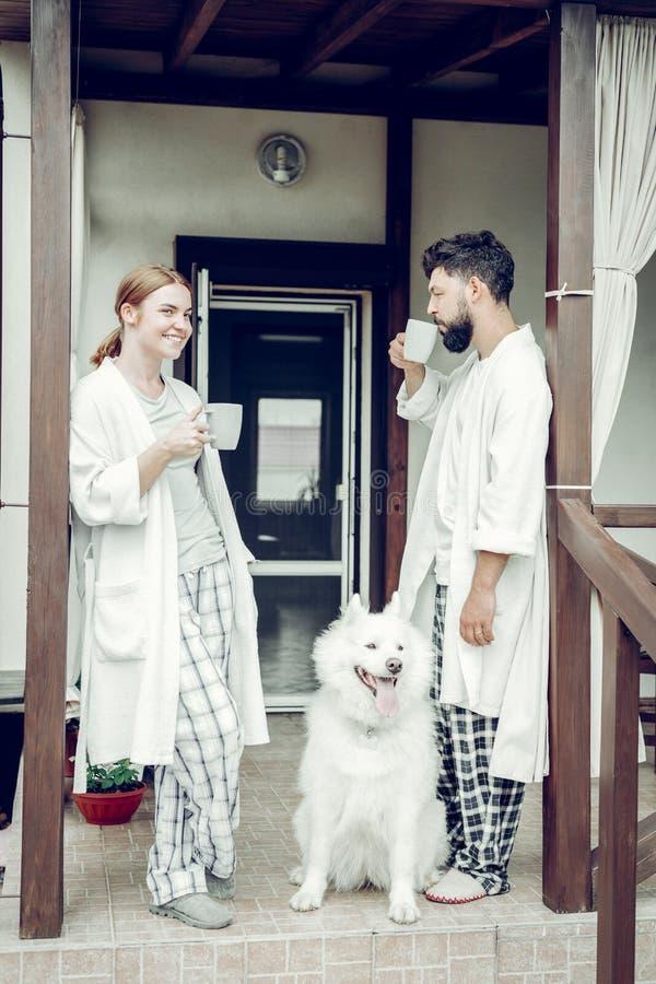Vrolijke glimlachende goed-een beroep doet slaperige man en vrouwen het drinken ochtendkoffie stock afbeelding