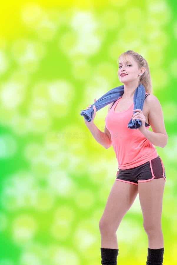 Vrolijke glimlachende jonge vrouw met handdoek na gymnastiekportret royalty-vrije stock afbeelding