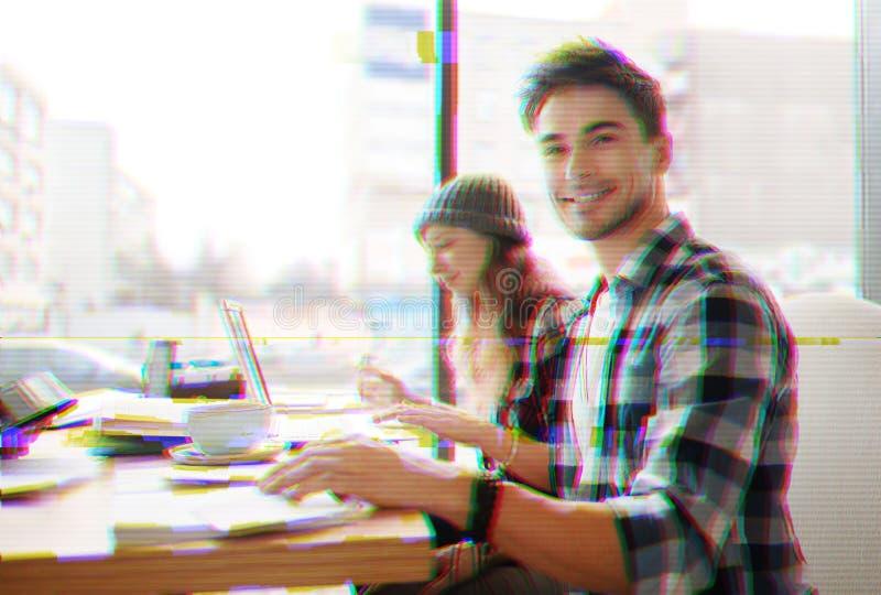 Vrolijke glimlachende studenten die in een koffie zitten en aan hun project werken royalty-vrije stock afbeelding